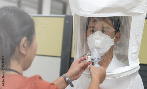 Fototapeta Respirator fit test prepared for COVID-19. Asia man testing repiratory system with N-95 surgical mask to checks properly fits face to wears. obraz