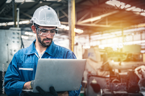 Confident engineer in blue jumpsuit holding laptop computer in a warehouse Fototapet