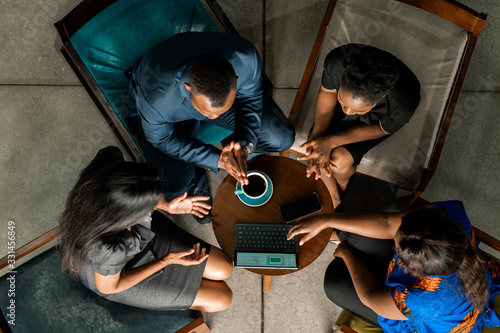 Obraz Black african start up business meeting shot from above. Overhead business people in brainstorming discussion - fototapety do salonu