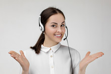 Beautiful Smiling Woman Consultant Of Call Center In Headphones On Gray Background. Female Customer Support Operator With Headset