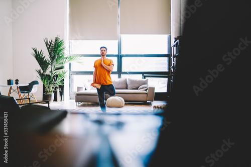 Photo Young man doing yoga asana at home