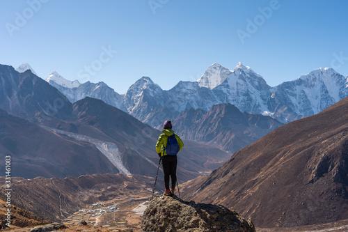 Fototapeta A trekker standing in front of Himalaya mountain range in Everest region, Nepal