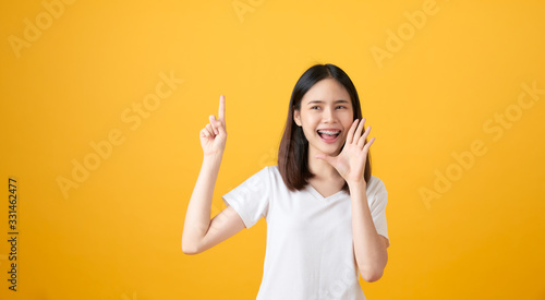 Photo Attractive young asian woman announcing with hands to the mouth  and telling a s