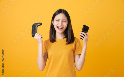 Cheerful beautiful Asian woman in casual yellow t-shirt and playing video games using joysticks and smartphone on orange background.