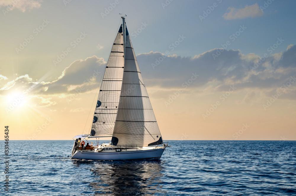Fototapeta close-up sailboat sailing under a beautiful sunset