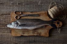 Sea Bass Fish On The Wooden Rustic Table With Scissors
