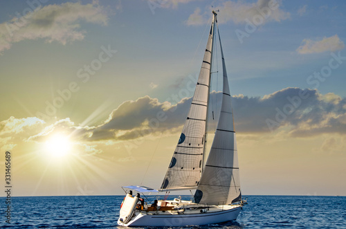close-up sailboat sailing under a beautiful sunset Fototapete