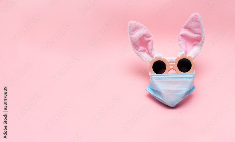 Fototapeta easter bunny in protective medical masks quarantine concept for easter holiday due to epidemic. Easter disease with preservation of positive. copy space, text. Bunny ears, sunglasses mask form face