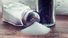 Glass Salt Shaker On Wooden Ba...