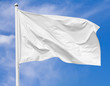 White flag waving in the wind on flagpole against the sky with clouds on sunny day, closeup