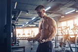 Muscular Fitness Bodybuilder Doing Heavy Weight Exercise For Biceps On Machine With Cable In The Gym.