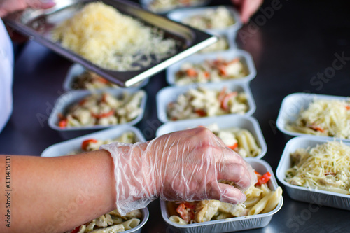 Fototapeta Food delivery. preparing food portions in containers. delivery service during quarantine covid-19. Chicken with vegetables and cheese. airline food. airline meals and snacks. takeaway selective focus obraz