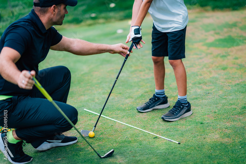 Fototapeta Golf – Personal Training. Golf Instructor Teaching Young Boy How to Play Golf. obraz