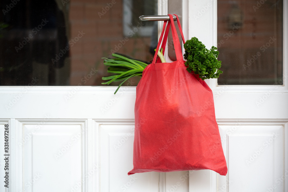 Fototapeta Shopping bag with goods and food is hanging at the front door, neighborhood help concept at quarantine time because of coronavirus infection, copy space