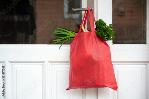 Shopping bag with goods and food is hanging at the front door, neighborhood help concept at quarantine time because of coronavirus infection, copy space