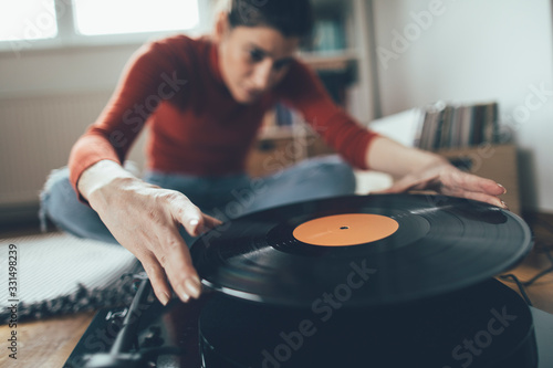 Photo Selective focus of audiophile playing favorite vinyl record on turntable