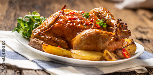 Foto Roasted chicken and american potatoes with chili peppers and herbs