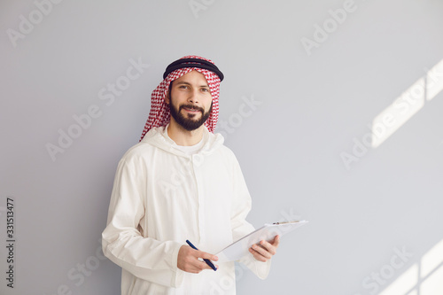 Papel de parede Attractive smiling arab man writes in clipboard on gray background
