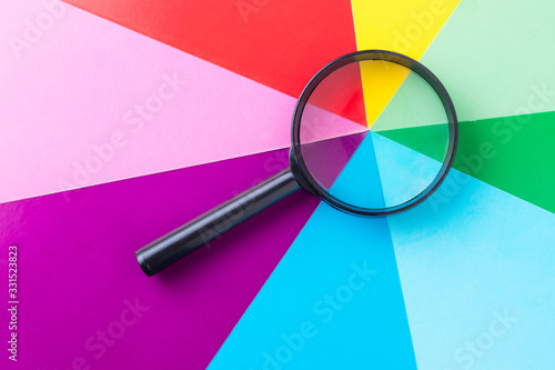 Fototapeta Magnifying glass on multi-colored sheets of paper. Search for diversity color combinations. The concept of finding a variety of choices. obraz