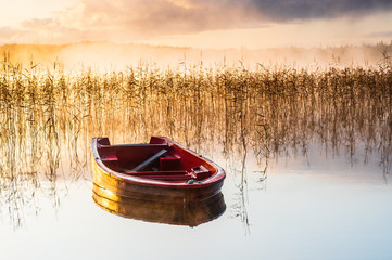 Obraz na Szkle Krajobraz Red boat on still misty lake at sunrise