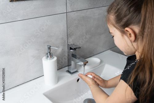 Fototapeta Dziewczynka myje ręce w łazience. Mycie i dezynfekcja rąk mydłem i płynem antybakteryjnym. obraz