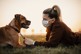 Fototapeta Zwierzęta - Woman wearing a protective mask is walking alone with a dog outdoors because of the corona virus pandemic covid-19