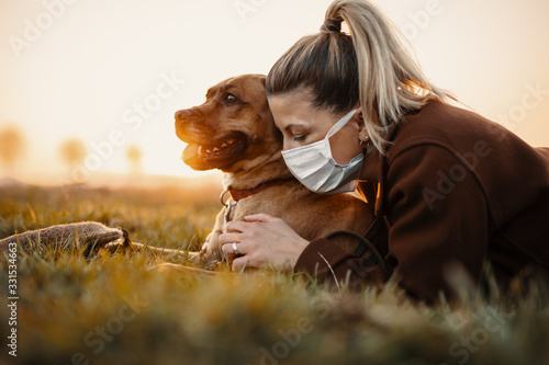 Woman wearing a protective mask is walking alone with a dog outdoors because of the corona virus pandemic covid-19