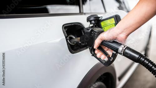 Obraz Tankowanie samochodu - dłoń w rękawiczce - fototapety do salonu