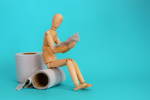Wooden Figure Sit On A Roll Of...