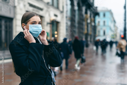 fototapeta na szkło Prevention of coronavirus outbreak in 2020. Portrait of young european woman wearing a mask in the city street. Prevent pollution and disease concept.