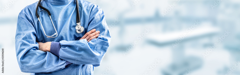 Fototapeta Young doctor surgeon specialist with scalpel. In the background blurred the interior of the operating room