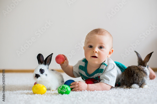Fototapeta Little toddler child, baby boy, playing with bunnies and easter eggs at home obraz
