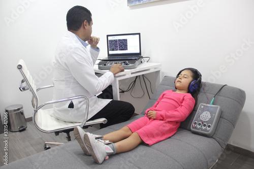 Leinwand Poster Examen medico auditivo a niña con doctor