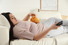 Lazy Overweight Woman With Chips Watching TV On Sofa At Home