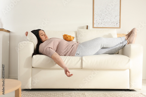 Lazy overweight woman with chips resting on sofa at home Canvas Print
