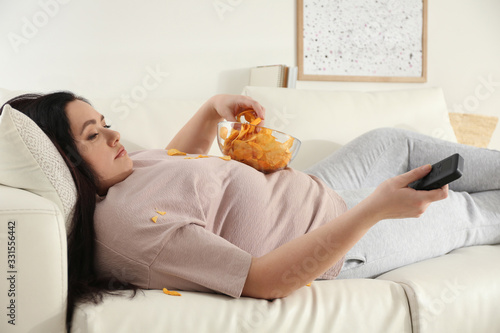 Photo Lazy overweight woman with chips watching TV on sofa at home