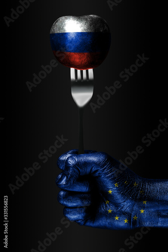 A hand with a drawn EU flag holds a fork, on which is a ball with a drawn Russia flag, a sign of influence, pressure, grip and anecxia Wallpaper Mural