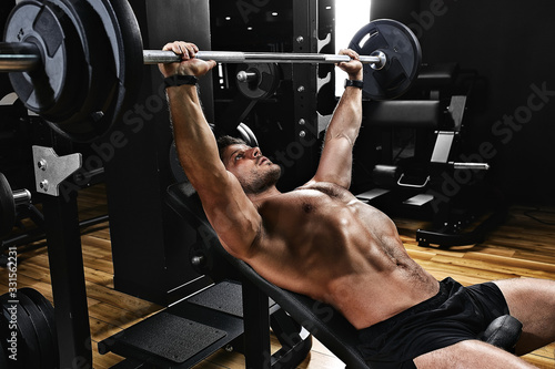 Fototapeta handsome young man doing bench press workout in gym, Fitness motivation, sports lifestyle, health, athletic body, body positive. Film grain, selective focus