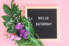 Hello Saturday Text On Black Letter Board And Bouquet Colorful Flowers On Pink Background. Concept Happy Saturday. Template For Postcard, Greeting Card Flat Lay Top View