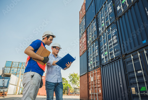 Obraz Foreman and dock worker staff working checking at Container cargo harbor holding clipboard. Business Logistics import export shipping concept. - fototapety do salonu