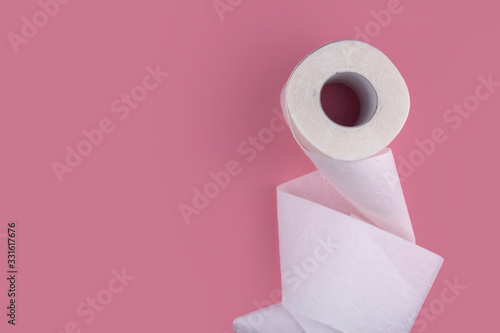 Fototapeta A roll of white toilet paper on a pink background copy space