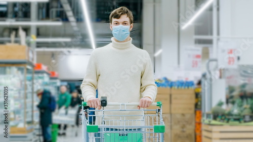 Photo A man in a medical mask stands in a supermarket with a food cart timelaps