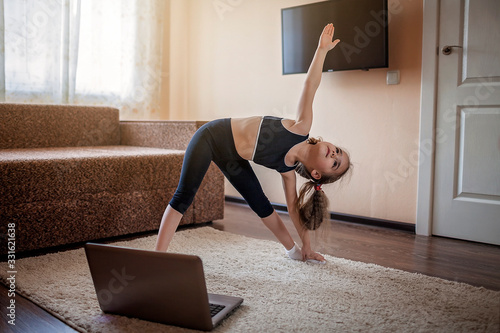 Foto Pretty young girl in sportswear watching online video on laptop and doing fitnes