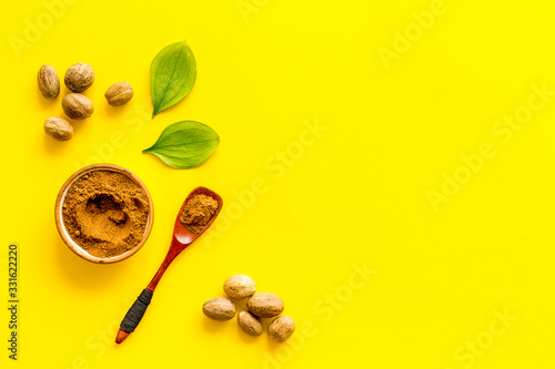 Fototapeta Nutmeg - spices in powder and whole nuts - on yellow background top-down copy space obraz