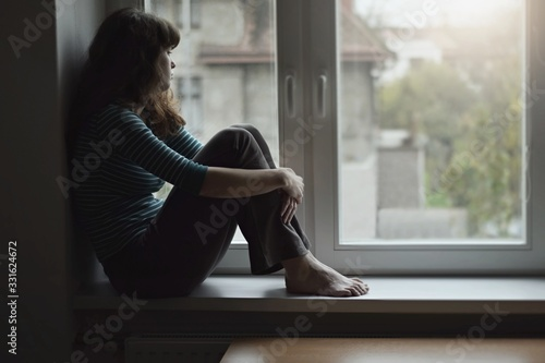 Sad young beautiful woman sitting on the window at home isolated, watching out. Coronavirus quarantine concept.