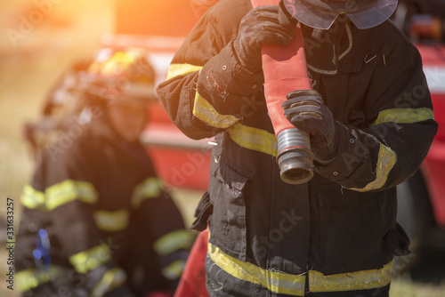 Firefighter in uniform and helmet near fire engine.