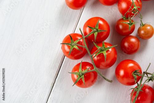 Fototapeta Pomodorini ciliegino freschi su tavolo in legno bianco obraz
