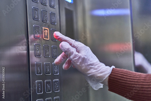Fototapeta Person in transparent rubber protective gloves presses the elevator button. Protection against viruses, germs and bacteria obraz