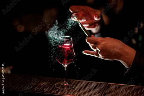 Obraz barman's hand professionally decorates alcoholic cocktail with colored powder using brush. - fototapety do salonu