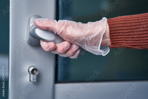 Person in transparent protective gloves holds handle during flu covid outbreak and infectious coronavirus epidemic Tableau sur Toile